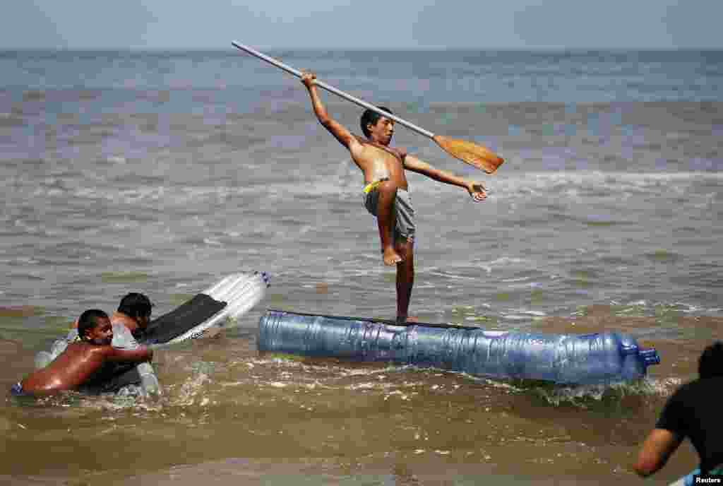A boy falls off a paddle board made with plastic bottles during a surfing lesson at a beach in Lima, Peru, Feb. 27, 2014.