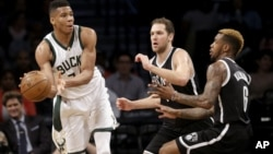 Giannis Antetokounmpo de Milwaukee, à gauche, contre deux Brooklyn Nets, Barclays Center, New York, le 13 mars 2016.