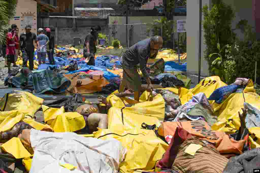 People attempt to identify the bodies of their relatives at the compounds of a police hospital in Palu, Indonesia's Central Sulawesi following a strong earthquake in the area. The death toll from a powerful earthquake and tsunami leapt to 832 as stunned people on the stricken island of Sulawesi struggled to find food and water and looting spread.