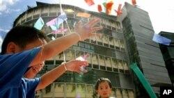 Anak-anak bermain di depan gedung Universitas Manajemen Singapura. (AP/Wong Maye-e)