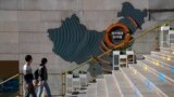 A family walks by a map showing Evergrande development projects in China at an Evergrande city plaza in Beijing, Sept. 21, 2021.