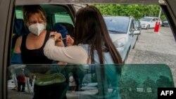Una mujer recibe una vacuna de Pfizer / BioNTech contra COVID-19 en un automóvil en un centro de vacunación en Pilsen, República Checa, el 21 de mayo, 2021.