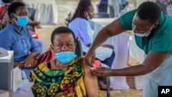 FILE - A woman receives a coronavirus vaccination at the Kololo airstrip in Kampala, Uganda, May 31, 2021.