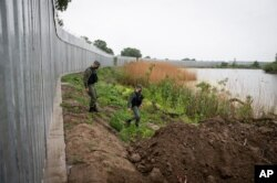 Police officers patrol alongside a steel wall at Evros river, near the village of Poros, at the Greek -Turkish border, Greece, May 21, 2021.