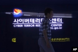 FILE - A man walks by a sign at Cyber Terror Response Center of National Police Agency in Seoul, South Korea, July 16, 2013. North Korea is accused of using cyberattacks against South Korea and 16 other countries to benefit its nuclear program.