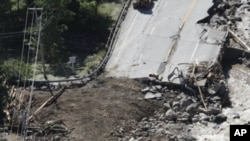 People gather alongside workers making repairs on Route 4 in Killington, Vermont, Aug. 30, 2011