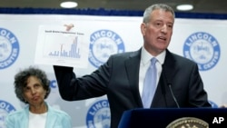 New York City Mayor Bill de Blasio holds up a chart documenting the cases of Legionnaires' disease while speaking to reporters at Lincoln Hospital in the Bronx borough of New York, Aug. 4, 2015.