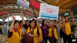 Tourists pose for a photograph at the departure hall of the China-Zhuhai-Macau-Hong Kong Bridge during the first day operation of the world's longest cross-sea project, which has a total length of 55 kilometers (34 miles), in Hong Kong, Oct. 24, 2018.