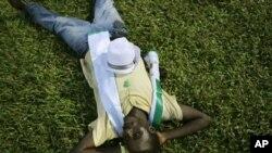 A supporter of opposition candidate Julius Maada Bio naps under stadium lights at rally, Freetown, Sierra Leone, Nov. 15, 2012.