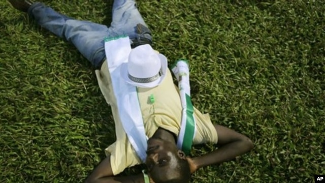 A supporter of opposition candidate Julius Maada Bio naps under stadium lights at rally, Freetown, Sierra Leone, Nov. 15, 2012.
