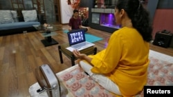 Yoga often involves deep breathing. In Ahmedabad, India, a woman takes an online yoga class in her house on International Yoga Day during the coronavirus outbreak, June 21, 2020. (Reuters Photo/Amit Dave)