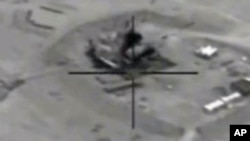 In this framegrabbed image provided by the U.S. Department of Defense shows airstrike footage on the Jeribe West Refinery in Syria Wednesday Sept. 24, 2014.