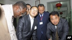 Chinese Embassy representatives sign handover papers to receive the body of a Chinese worker killed during a kidnapping, from a Sudanese Red Crescent representative (L) and a Sudanese Foreign Ministry official at the Chinese-run Hawasha hospital, in Khart