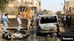 이라크 보안 요원들이 5일 차량 폭탄 공격 현장을 조사하고 있다.
