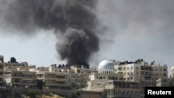 Khói bốc lên từ khu nhà trong quận El Edaa sau cuộc oanh kích của lực lượng không quân Syria