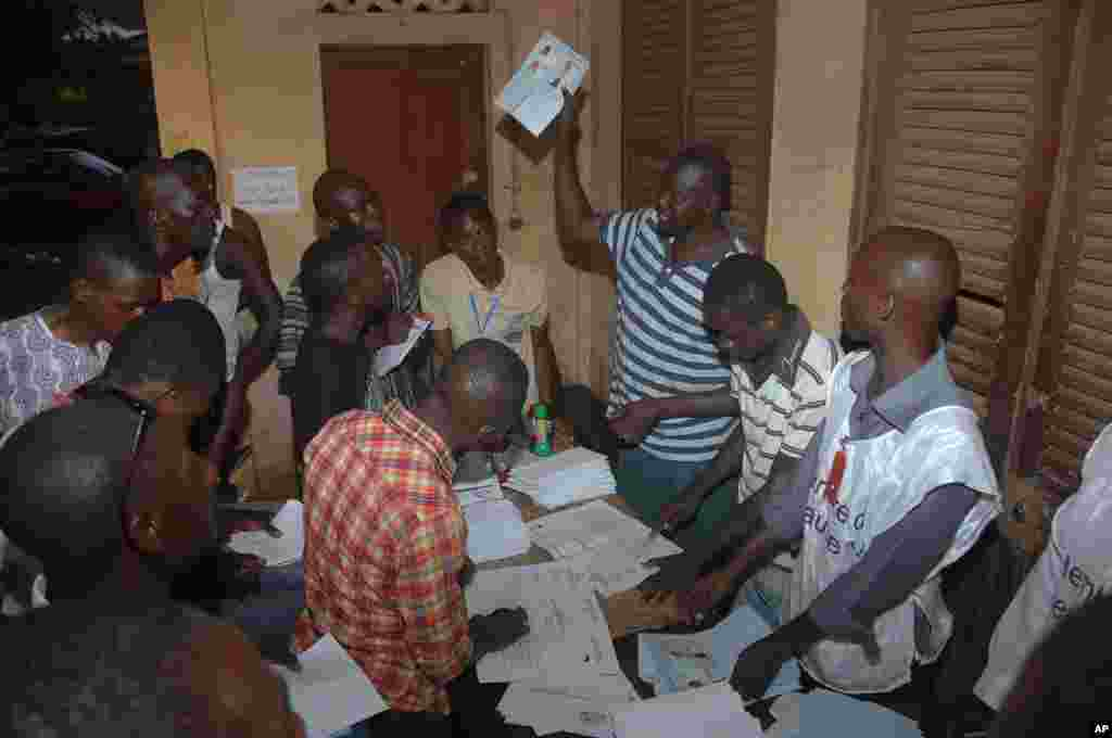 Election workers count legislative ballots after the close of voting, at a polling station in Conakry, Guinea, Sept. 28, 2013.