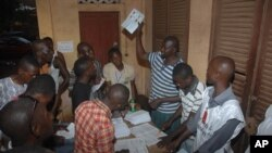Le personnel électoral dépouillant les votes après la clôture du scrutin, à un bureau de vote à Conakry, en Guinée, le 28 septembre 2013.