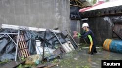 Một người đàn ông dọn dẹp các mảnh vỡ gần căn nhà bị ngập lụt vì bão Saola ở Wujie trong quận Ilan ở Ðài Loan, ngày 2/8/2012