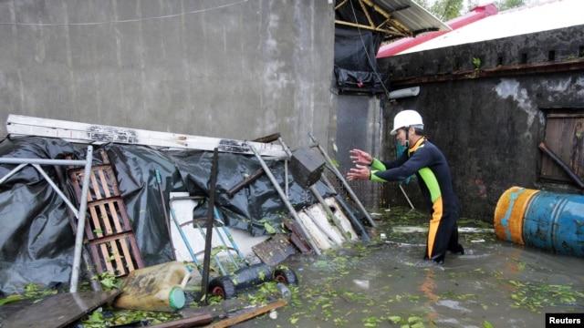 A man clears debris near his house flooded by Typhoon Saola in Wujie in Ilan County, Tawian, August 2, 2012.