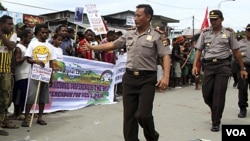 Polisi berjalan di depan masa yang berdemo di DPRD di Abepura, Papua. (Foto:dok)
