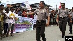 Polisi berjalan di muka para demonstran ketika berlangsung protes di luar gedung DPRD di Abepura, Jayapura (2/8).