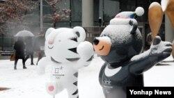 한국 서울의 눈 내린 거리에 평창올림픽 마스코트인 수호랑과 반다비가 서 있다.
