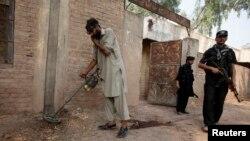 Seorang petugas keamanan menggunakan metal detektor untuk memeriksa lokasi ledakan bom di Peshawar, Pakistan (7/10).
