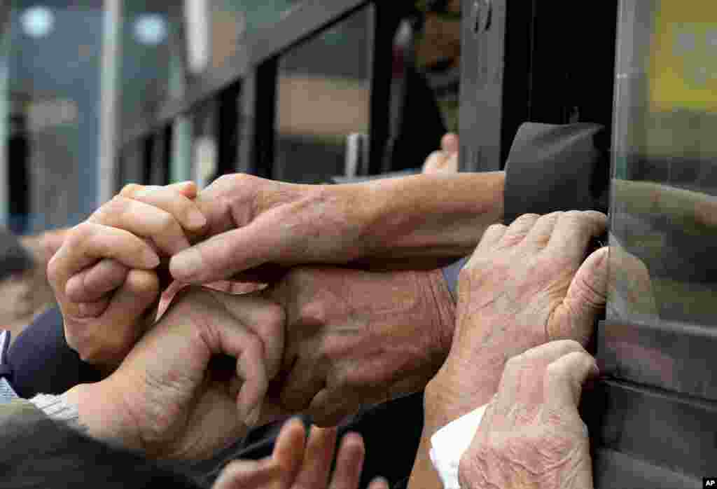 South Koreans and their North Korean relatives on a bus grip each other's hands to bid farewell after the Separated Family Reunion Meeting at Diamond Mountain resort in North Korea. About 390 South Koreans traveled to the North's scenic Diamond mountain resort earlier this week to meet for three days with relatives they were separated from during the turmoil of the 1950-53 Korean War.