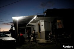 FILE - People gather to chat outside a mini-market that uses electricity from a generator, at the squatter community of Villa Hugo in Canovanas, Puerto Rico, December 12, 2017.