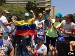 Venezuelan anti-government protesters including activist Lilian Tintori, center right in printed T-shirt, demonstrate in Caracas, April 20, 2017. Tintori's shirt bears a likeness of her husband, jailed opposition leader Leopoldo Lopez. (A. Algarro/VOA)
