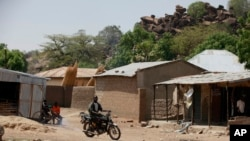FILE - In this Monday, May 19, 2014 photo, an unidentified man rides a motorbike past houses in Chibok, Nigeria. Multiple suicide bombings have killed a number of civilians and a soldier and the toll is expected to rise among those critically wounded in the Chibok, community leaders said Thursday Jan. 28, 2016 in the town from which Boko Haram kidnapped scores of schoolgirls almost two years ago.
