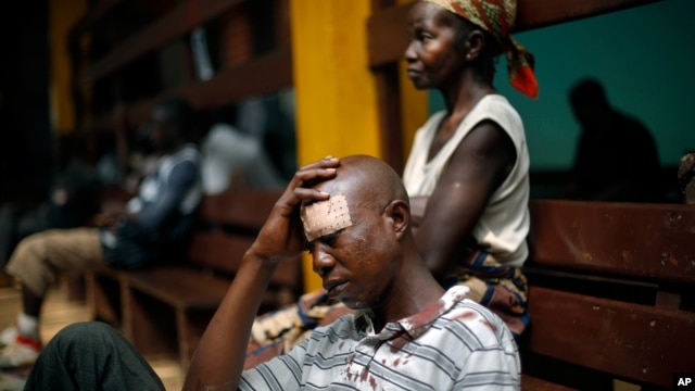 A man wounded in fighting between anti-Balaka and ex-Seleka troops sits on the floor in the Community Hospital in Bangui, Central African Republic, Dec. 20, 2013.