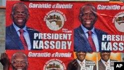Un homme collant des affiches électorales à Conakry