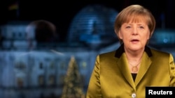 FILE - German Chancellor Angela Merkel poses for photographs after the recording of her annual New Year's speech at the Chancellery in Berlin, Dec. 30, 2013.