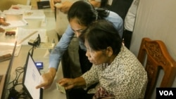 Voter registration official talks to an eligible voter to verify detail information for her to register for the local elections next year, in Phnom Penh, on Thursday, September 1, 2016. (Hean Socheata/VOA Khmer)