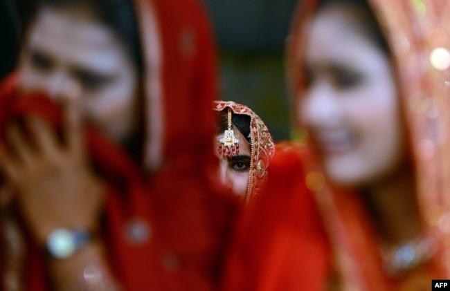 FILE - Pakistani brides attend a mass marriage ceremony in Karachi.