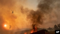 FILE - In this Sunday, Aug. 5, 2018, file photo, a helicopter drops water on a burning hillside during the Ranch Fire in Clearlake Oaks, Calif. Authorities say a rapidly expanding Northern California wildfire burning over an area the size of Los Angeles has become the state's largest blaze in recorded history. It's the second year in a row that California has recorded the state's largest wildfire. (AP Photo/Josh Edelson, File)