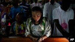 Umat Katolik Kongo mendengarkan Monsinyur Fridolin Ambongo, Uskup Agung Kinshasa yang baru diangkat, memberikan khotbah Natal pada misa tengah malam di Katedral Notre Dame Kongo di Kinshasa, Kongo, Senin, 24 Desember 2018.