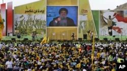 Pendukung pemimpin Hizbullah, Hassan Nasrallah, menonton tayangan pidatonya di Mashghara, Bekaa Valley, Lebanon (25/5). (AP/Hussein Malla)