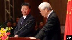 Chủ tịch Trung Quốc Tập Cận Bình nhìn Tổng bí thư Việt Nam Nguyễn Phú Trọng phát biểu trong chuyến thăm Việt Nam cuối năm 2015.