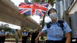 A pro-democracy supporter waves a British flag as police officers stand guard outside a court in Hong Kong Thursday, April 1, 2021. (AP Photo/Vincent Yu)