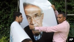 Workers uninstall a billboard showing presidential candidate Ahmed Shafiq in Cairo.