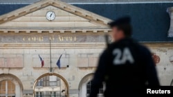 FILE - A police officer secures the entrance of the Appeals Court of Versailles for the arrival of vehicles transporting Mehdi Nemmouche, the French national suspected of the shooting attack in the Brussels Jewish Museum in May that left four people dead.