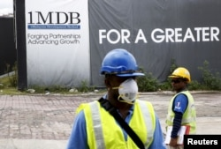 FILE - Construction workers stand in front of a 1Malaysia Development Berhad (1MDB) billboard at the Tun Razak Exchange development in Kuala Lumpur, Malaysia.