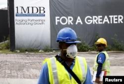 FILE - Construction workers stand in front of a 1Malaysia Development Berhad (1MDB) billboard at the Tun Razak Exchange development in Kuala Lumpur, Malaysia, Feb. 3, 2016.