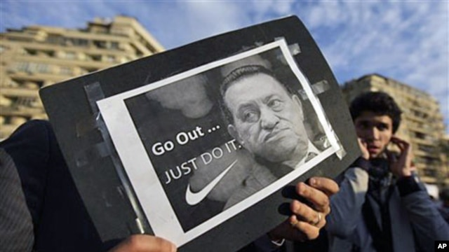 "A protester holds a placard showing Egyptian President Hosni Mubarak and reading ""Go out... Just do it"" at the continuing anti-government demonstration in Tahrir Square in downtown Cairo, Feb 10 2011"