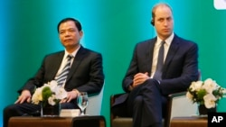Vietnam's Minister of Agriculture Nguyen Xuan Cuong, left, and Britain's Prince William, Duke of Cambridge, right, listen to a speech at an international conference on illegal wildlife trade in Hanoi, Vietnam, Nov. 17, 2016.