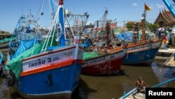 A fisherman man sits on a pier near docked fishing boats at a port in Thailand July 1, 2015. Thai fishermen went on strike to protest regulations aimed at clamping down on illegal fishing.