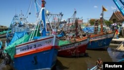 FILE - A fisherman sits as fishing vessels are seen docked after fishing operations stopped at a port in Samut Sakhon province, Thailand.