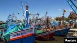 Kapal-kapal nelayan berlabuh setelah operasi-operasi penangkapan ikan dihentikan, di sebuah pelabuhan di provinsi Samut Sakhon, Thailand.